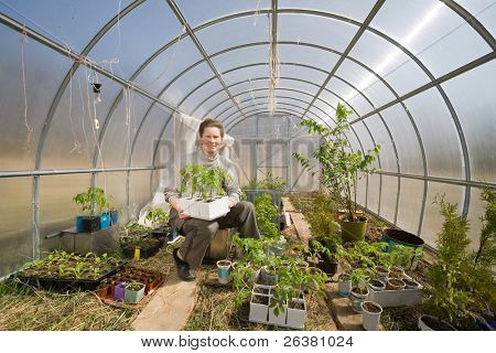 Old woman sitting in greenhouse looking after different plants