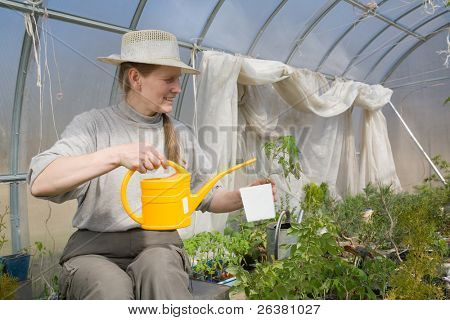 Woman in years sitting in greenhouse with watering-pot and watering plants