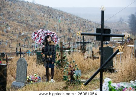 a girl standing at a cemetery under umbrella