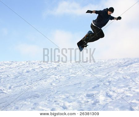 Young man on snowboard on the slope of mountain at sunny day