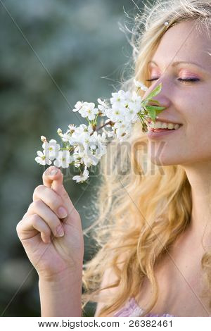 Smiling woman with branch of blooming tree at spring park