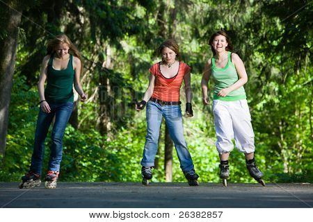 Three women on rollerblades at park