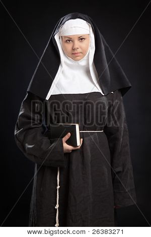 Portrait of young  nun holding a bible