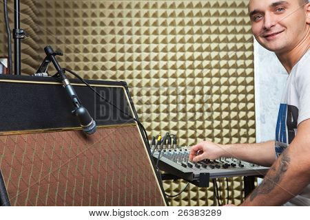 Homem na gravação de sessão de estúdio na frente da placa do mixer. Amplificador de guitarra em primeiro plano