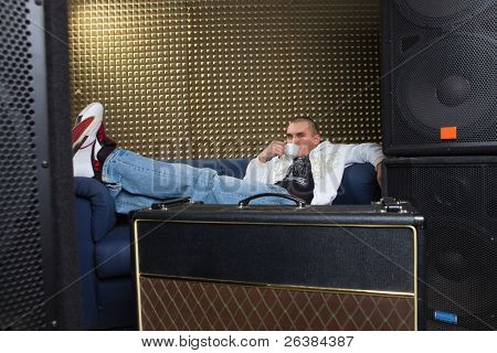 Man in recording studio sitting at sofa and drinking coffee