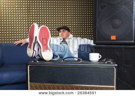 Man in recording studio sitting at sofa and drinking cofe