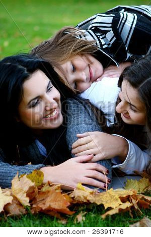 Young family taking healthy stroll through autumn park and have fun