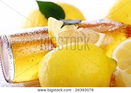 Bottle of cold beer with fresh yellow lemons on white background