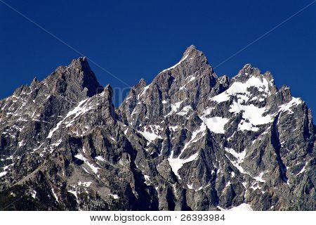 grant tetons, peaks against blue sky
