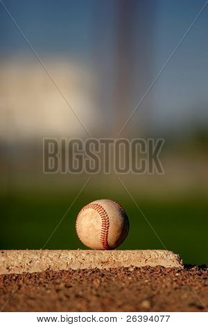 baseball close up on pitcher's mound, late afternoon sun