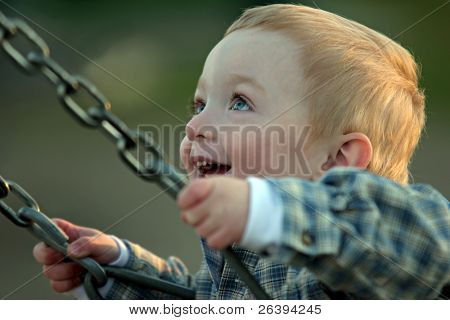 cute young redheaded boy on a swing, pure joy. shallow depth of field with focus on his left eye.