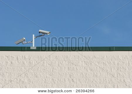 two video surveillance cameras ccd on the edge of a rooftop - white wall, blue sky with copyspace