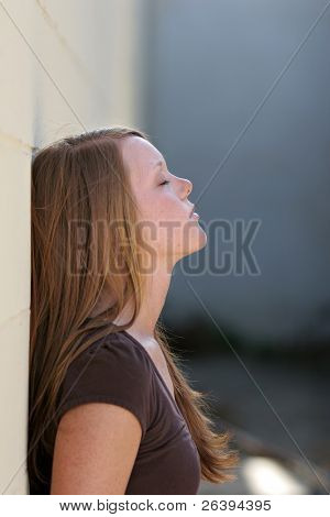 pretty young girl leaning against wall. tired, giving up, showing resignation