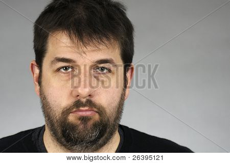 Somber Bearded Man Over Grey