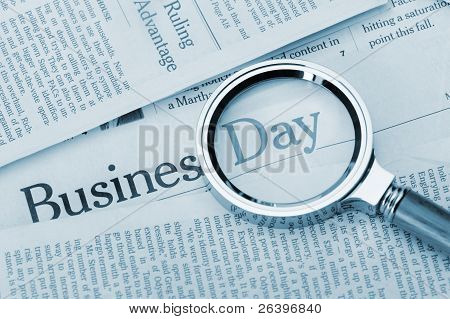 Loupe Lies On The Newspaper With Title Business Day. Blue Toned