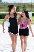 Two women enjoying a game of beach volleyball poster