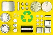 Green Recycle Reuse Sign Symbol With Metal Aluminium Cans, Covers, Jars On Yellow Background. Eco Ec poster