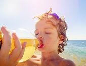 Close Up Side View Of Cute Kid Drinking Cold Drink On The Beach, Little Boy Drinking Sweet Carbonate poster