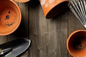 Group Of Empty, Used Terracotta Planting Pots With Gardening Tools On Wooden Table From Above Top Vi poster
