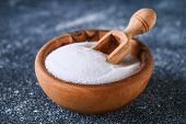 Crystals Of Shallow Salt In A Wooden Bowl On A Dark Gray Table. Background For Advertising Salt. Tab poster