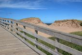 A boardwalk over the sand dunes to the beach in Cavendish National Park, Prince Edward Island, Canada poster