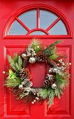 Christmas wreath with baubles, cones and evergreen boughs on a red door.