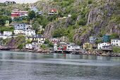 Colorful houses on the rocky shore of Signal Hill facing the harbour in St. John's, Newfoundland, Canada.  A section of town known as the Lower Battery. poster