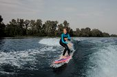 Smiling Teenager Boy Riding On The Orange Wakeboard Having Healthy Summertime On The River On The Ba poster