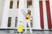 Excited Traveler Tourist Woman In Yellow Summer Casual Clothes And Hat With Suitcase Looking On City poster