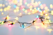 Christmas Lights In Warm Yellow White On String And Gold Xmas Balls Over Light Background With Copy  poster