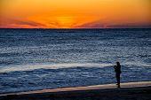 Surf fisherman on Florida beach as sunbeams light up the horizon poster