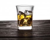 Whiskey glass or glass of whiskey with ice cubes on the table at white background. poster
