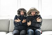 Couple Have Cold On The Sofa At Home With Winter Coat poster