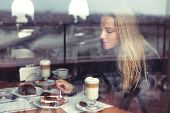 Nice female in cafe eating cake and drinking latte in warm cozy atmosphere, enjoying sweet tasty des poster