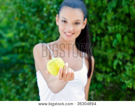 Beautiful girl offering a yellow apple outdoors