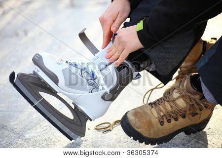 Tying laces of ice hockey skates skating rink