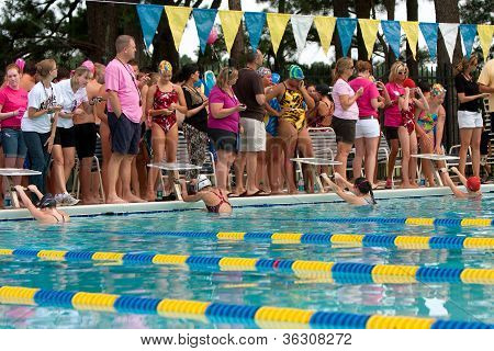 Junior Female Swimmers Ready To Start Backstroke Race