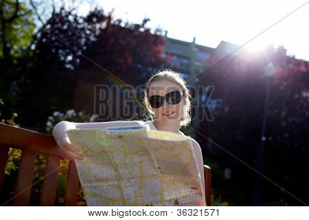 Girl reads the map outside