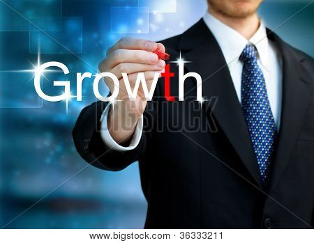 Young Business Man Writing The Word Growth