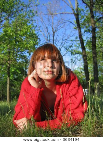 Red-Hair Girl Laying On The Grass