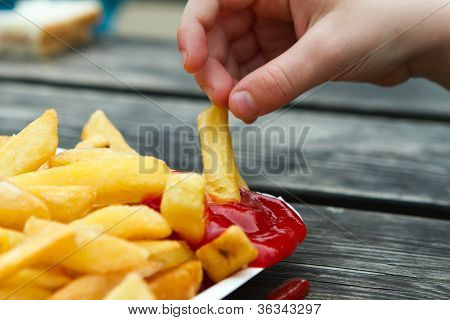 Child Dipping A Chip Into Tomato Sauce