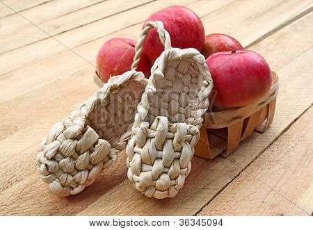 Rural Still Life With Apples And Sandals Made Of Bark