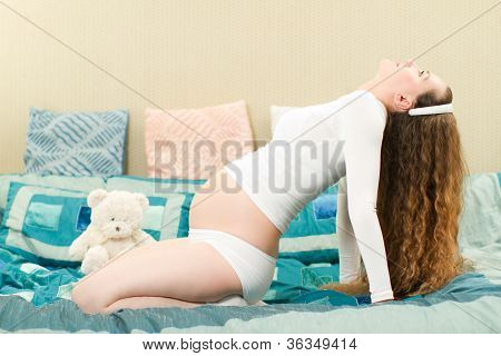 Pregnant Woman With Long Hair In A Yoga Pose On Sofa At Home