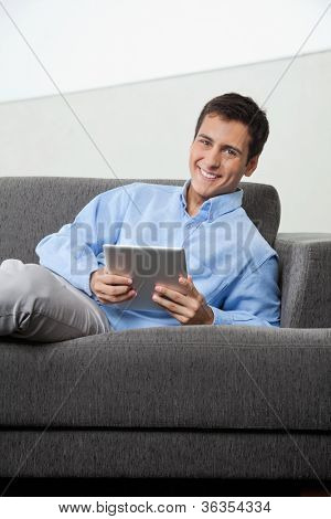 Portrait of happy young man in formal wear holding digital tablet while sitting on sofa