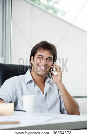 Portrait of happy male architect attending a phone call