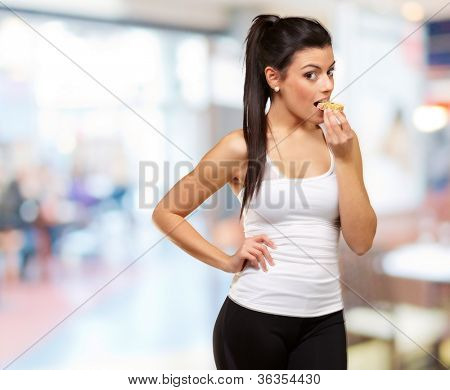 young healthy girl eating a cereal bar indoor