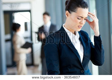 young businesswoman having headache at work