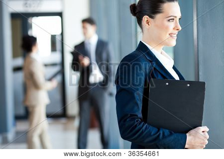attractive young businesswoman looking outside window