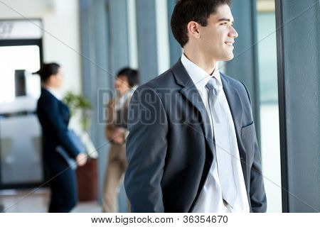 handsome young businessman looking outside office window
