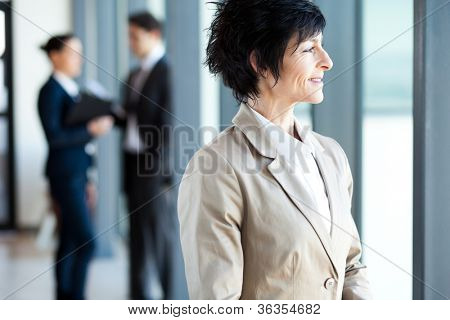 mature businesswoman looking outside office window